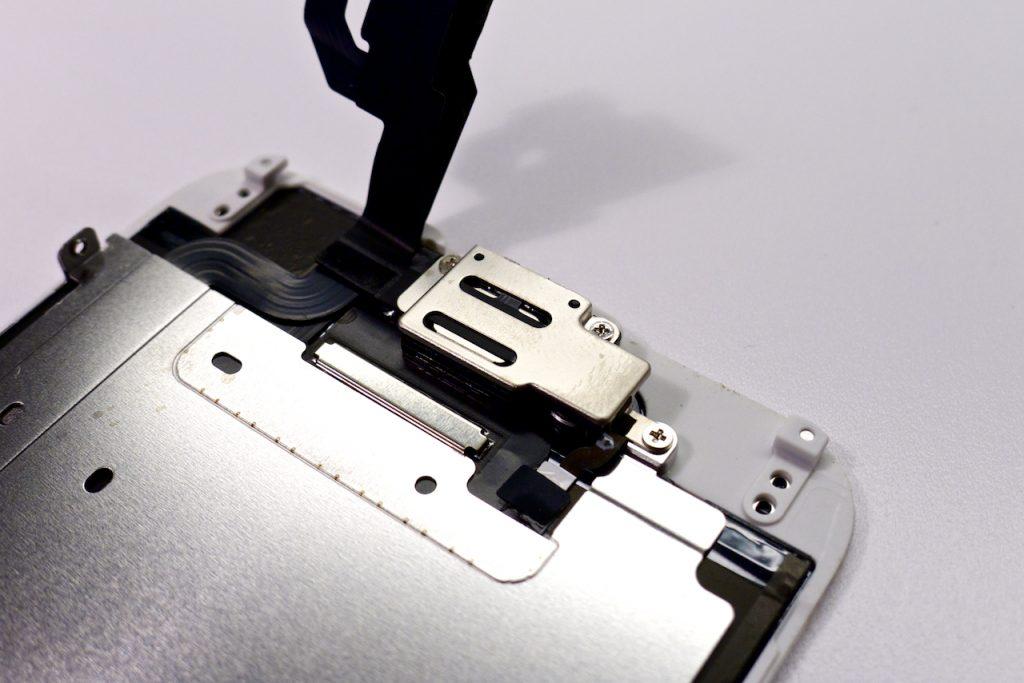 A kijelző felső részében található egy kamera, egy hangszóró, egy mikrofon, egy közelségérzékelő és egy fényérzékelő. iPhone 6 kijelző közelről, szétszedve