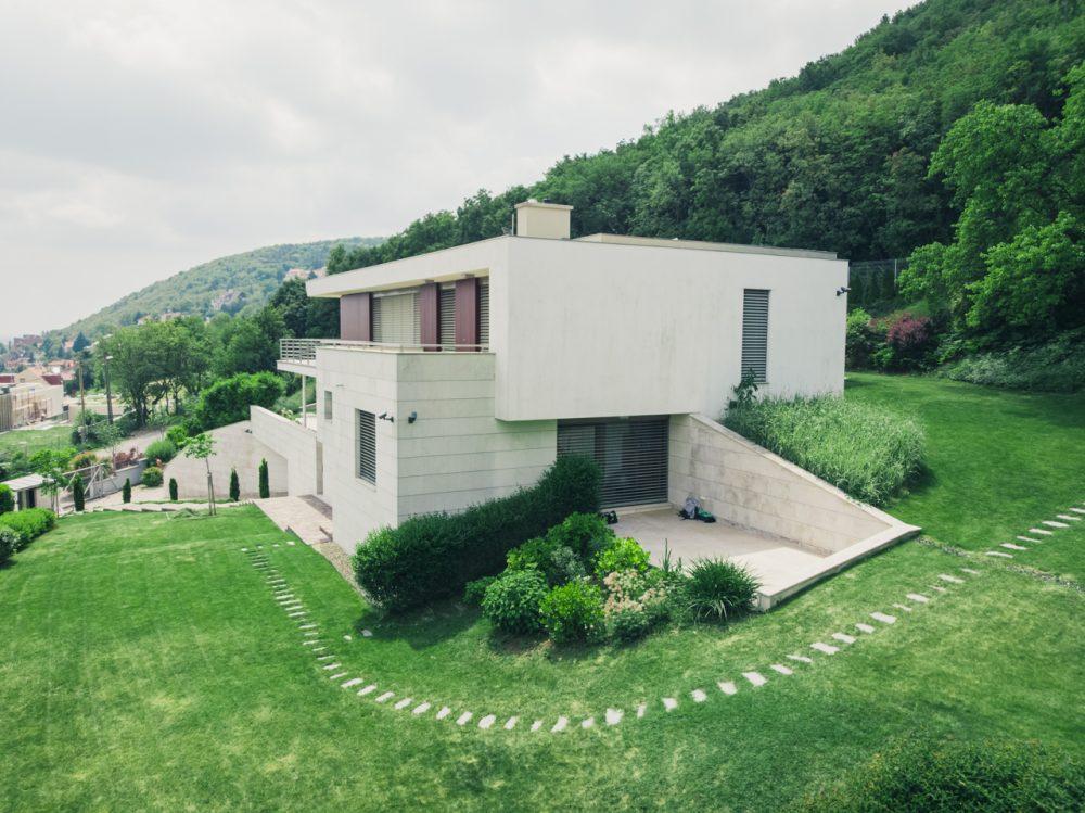 A szabályok közé szorított kert és a szabályokra fittyet hányó erdő határán épült ez a ház, drónfotók légifelvétel, légifotó