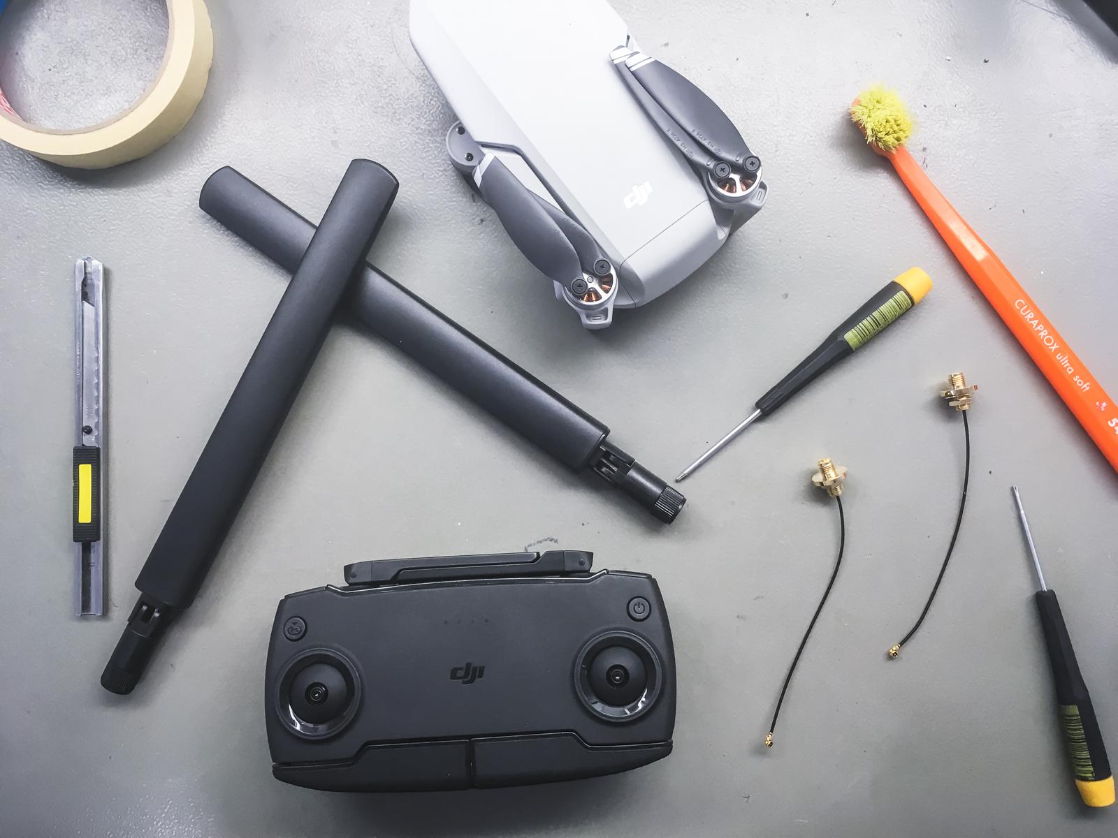 A Mavic Mini távirányítója átalakítás előtt, és mellette az új antennacsatlakozók és antennák.